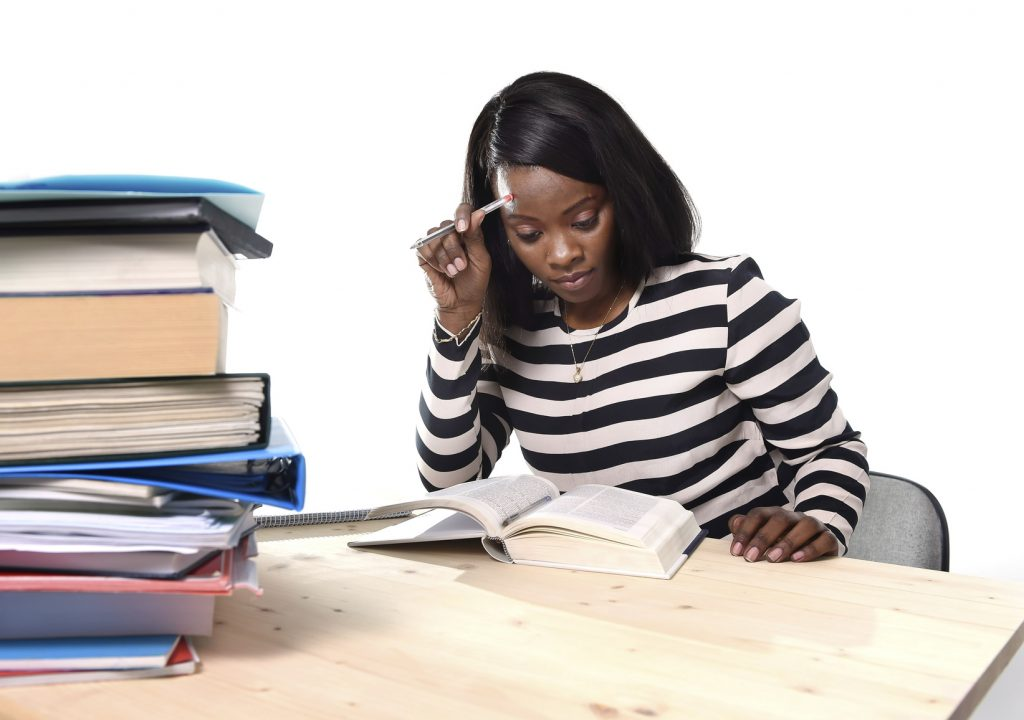 young black African American ethnicity student girl studying pile of books on library desk preparing exam in stress reading textbook concentrated in youth education concept